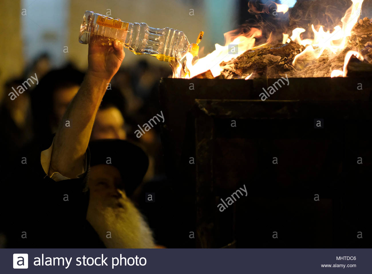 Jerusalem, Israel 02 May 2018. Ultra-Orthodox Jew pours oil into a bonfire in the Mea Shearim religious neighborhood during the celebration of Lag BaOmer holiday which marks the celebration, interpreted by some as anniversary of death of Rabbi Shimon bar Yochai, one of Judaism's great sages some 1800 years ago and the day on which he revealed the deepest secrets of kabbalah a landmark text of Jewish mysticism - Stock Image