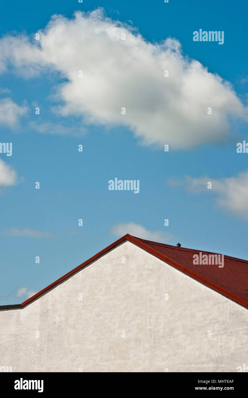 white wall and roof of a building against blue cloudy sky - Stock Image
