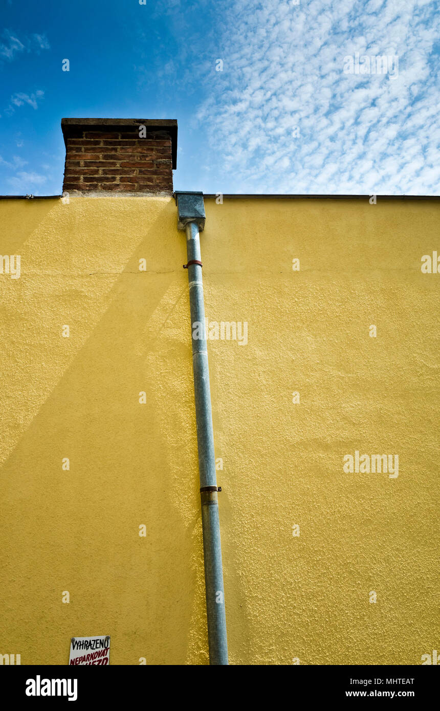 yellow wall with chimney and a water draining pipe - Stock Image
