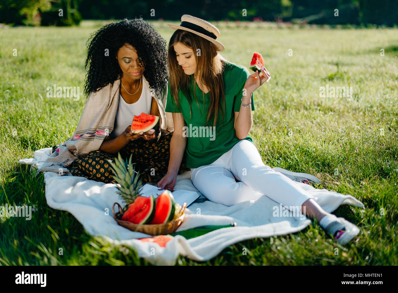 Timespending of two multi-ethnic girl friends.Pretty african girl is chatting via the mobile and eating the watermelon while her attractive blonde friend is reading book and eating fruit.Picnic theme. - Stock Image