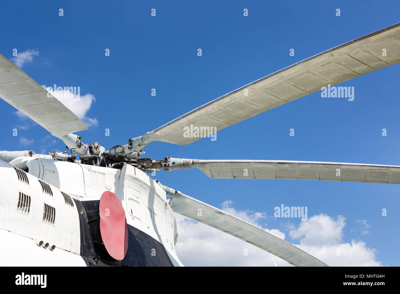 Close-up  blade rotors of big cargo-passenger helicopter against blue sky on background - Stock Image