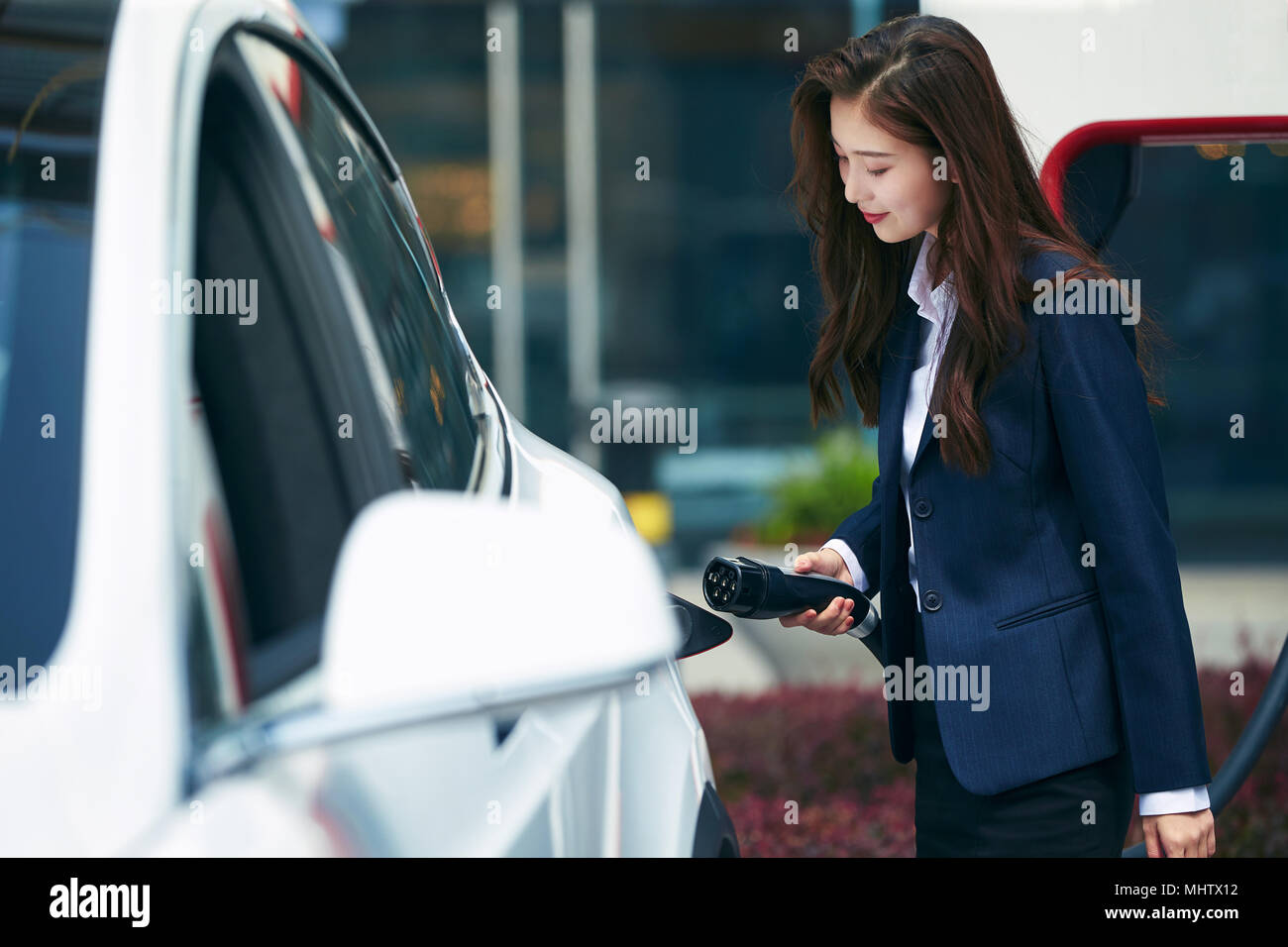 Young business woman to recharge electric cars - Stock Image