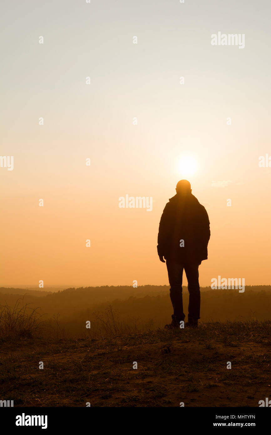 Rear view of a male figure watching the sunset from the mountain - Stock Image