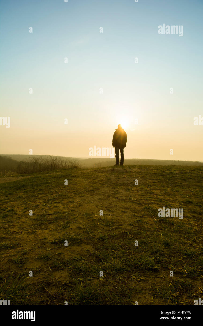 Rear view of a male figure standing on the field at sunset - Stock Image