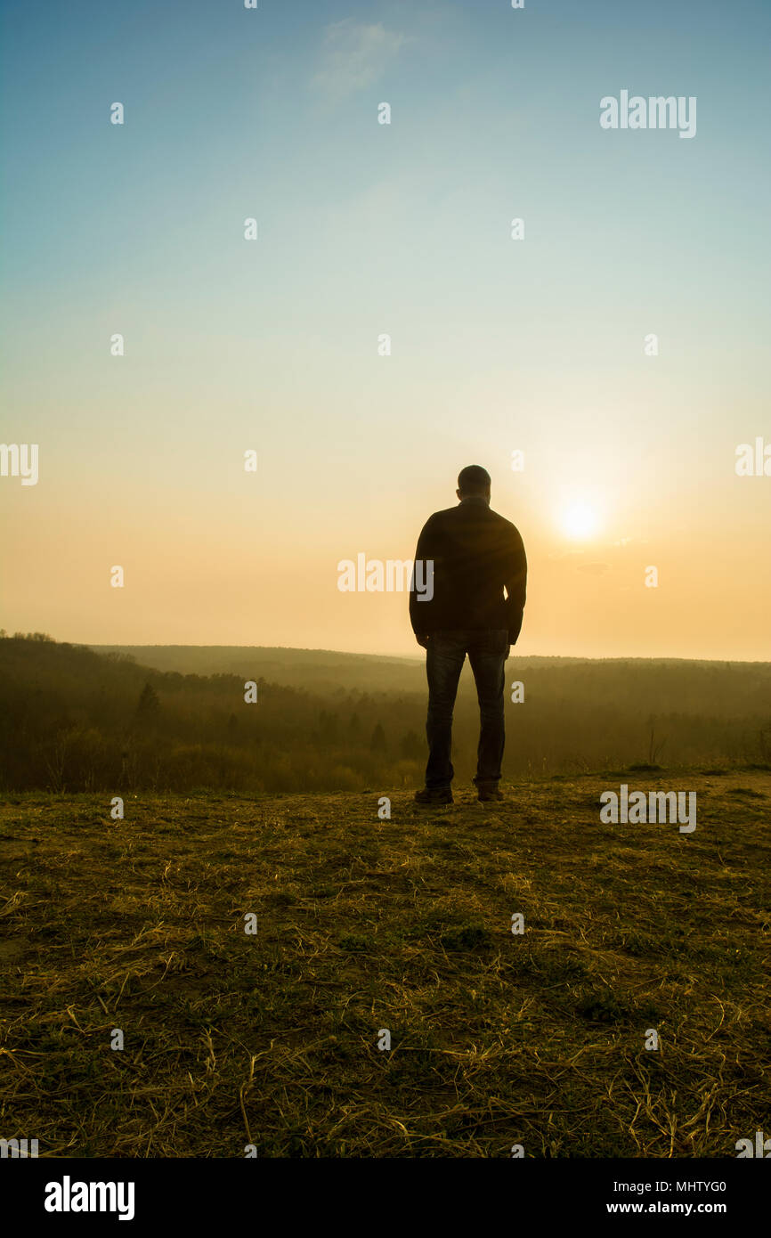 Rear view of a man watching the sunset from the top of a mountain - Stock Image