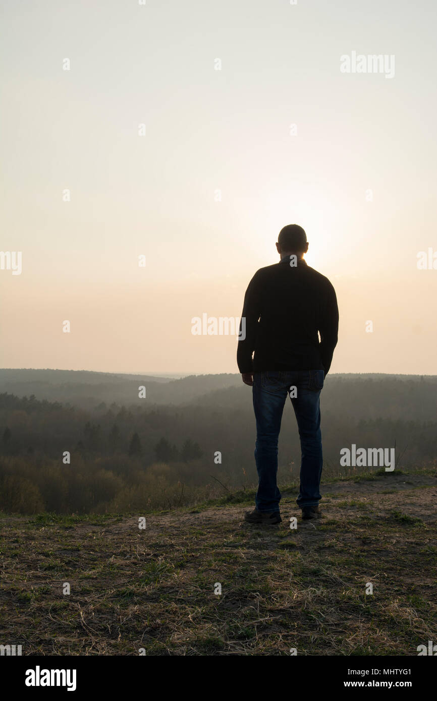 Rear view of a man standing on top of the mountain - Stock Image