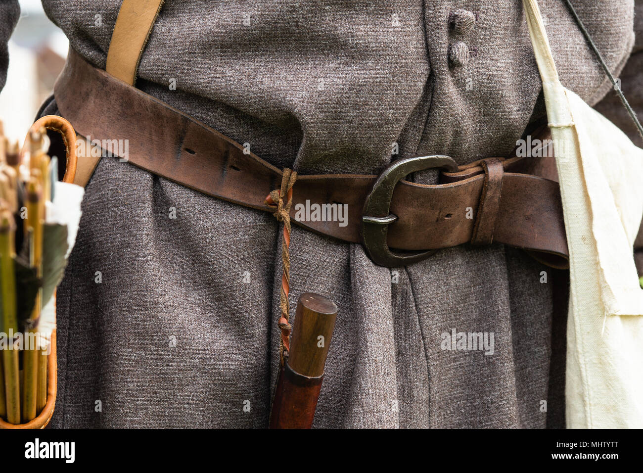 Details of a suit of a medieval archer. Leather belt, a knife and a quiver with a bunch of arrows are attached to a belt. A coarth texture of an overc - Stock Image