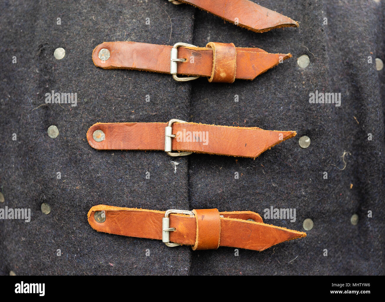 Leather fasteners or straps of a medieval knight overcoat made of the natural wool of grey color - Stock Image