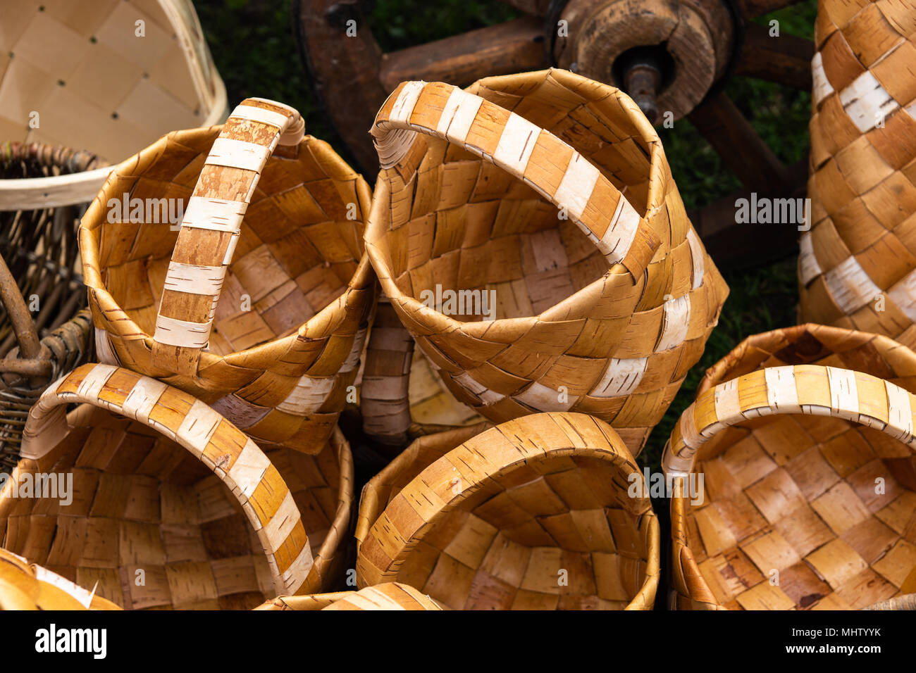 Brown wooden baskets made of a bast in a pile on the ground. Rural fair, vintage goods for sale - Stock Image