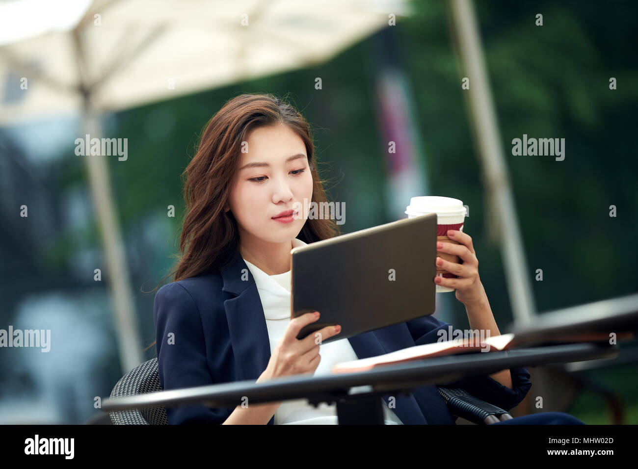 Young women to use a computer in a coffee shop - Stock Image