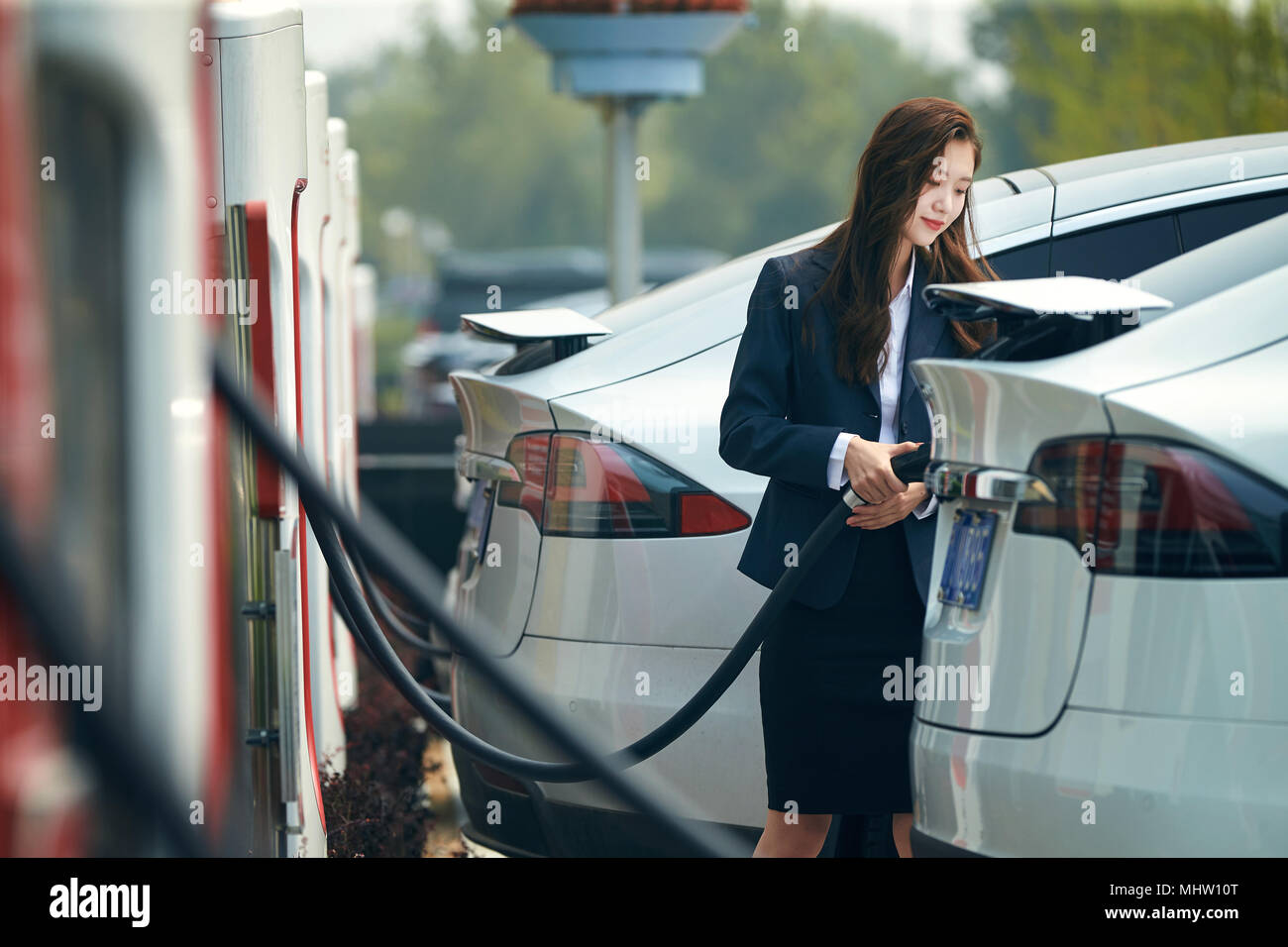 Young women to recharge electric cars - Stock Image