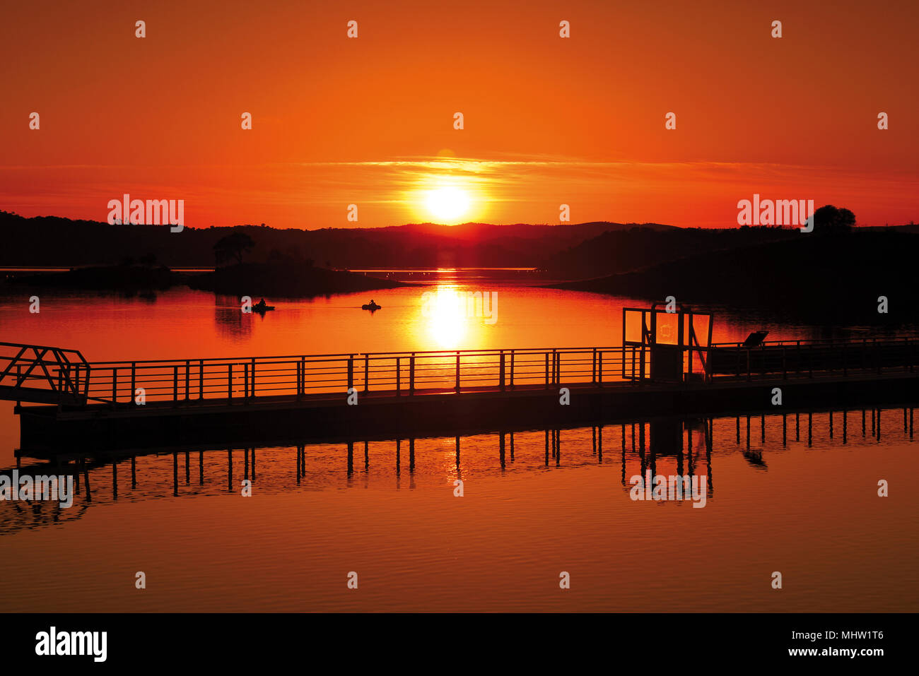 Scenic sunset  with orange horizon over lake with boat launch - Stock Image