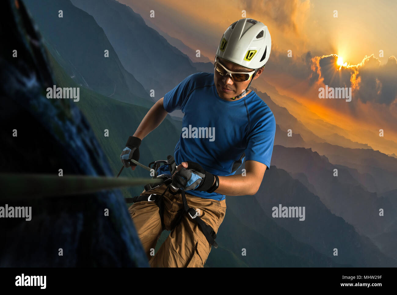 Middle-aged man climbing over a cliff - Stock Image