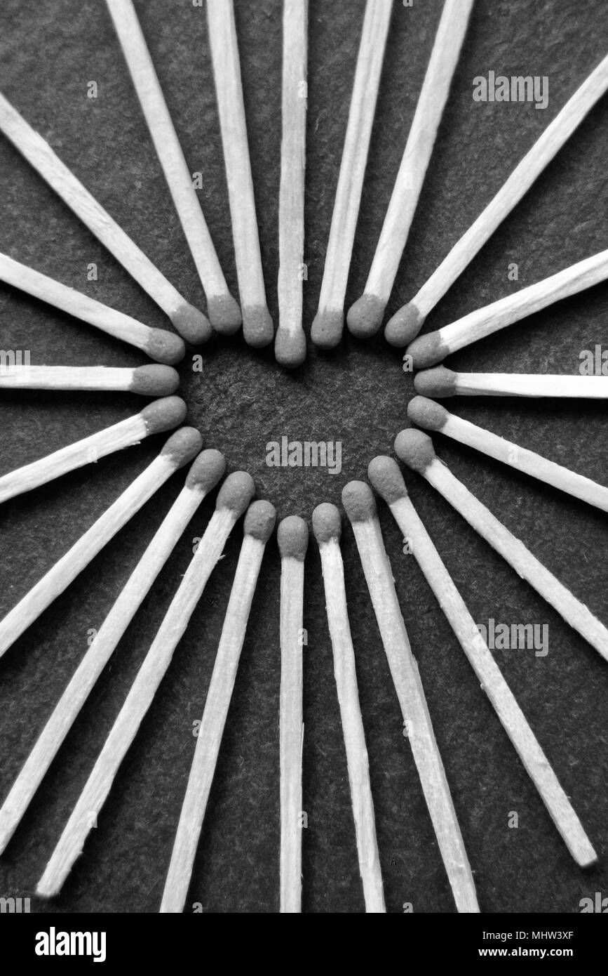 Black and white photo showing a collection of matches laid out in a heart forming shape on a black grey slate background. - Stock Image