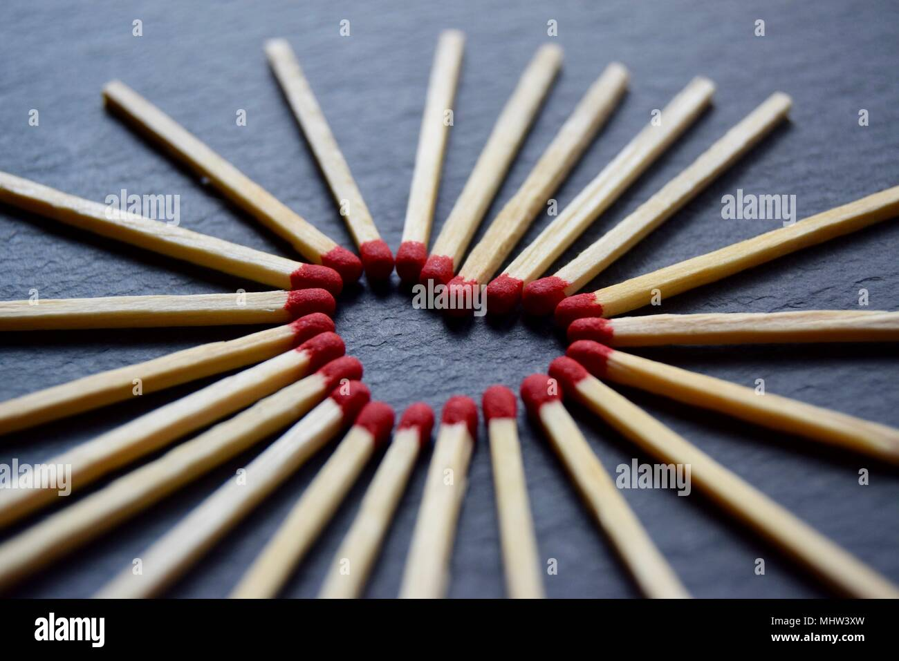 Collection of red head matches laid out in a heart forming shape on a black grey slate background. - Stock Image
