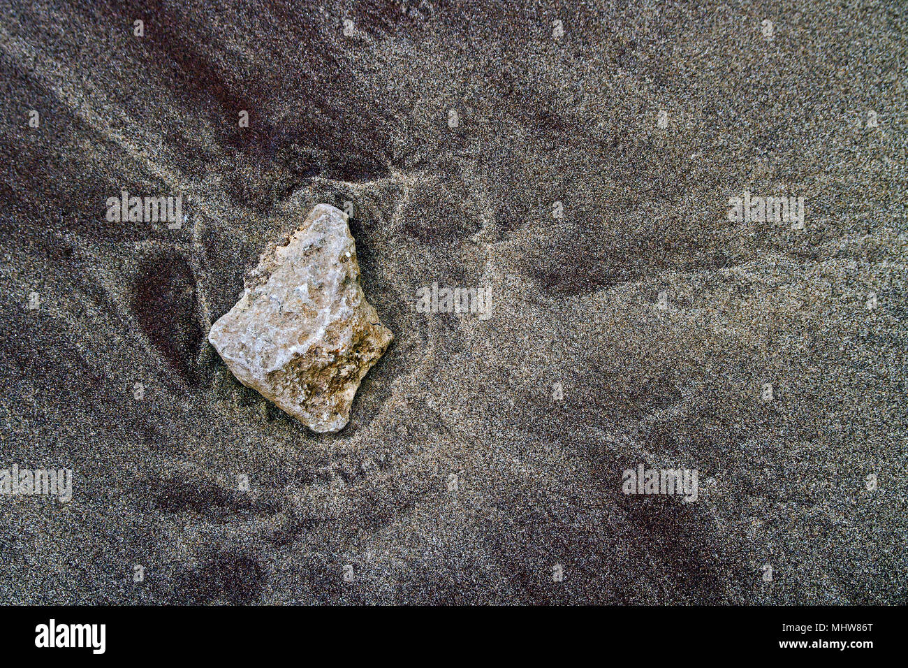 A solitary pebble deposited by the tide on a layer of dark-coloured sand. Stock Photo