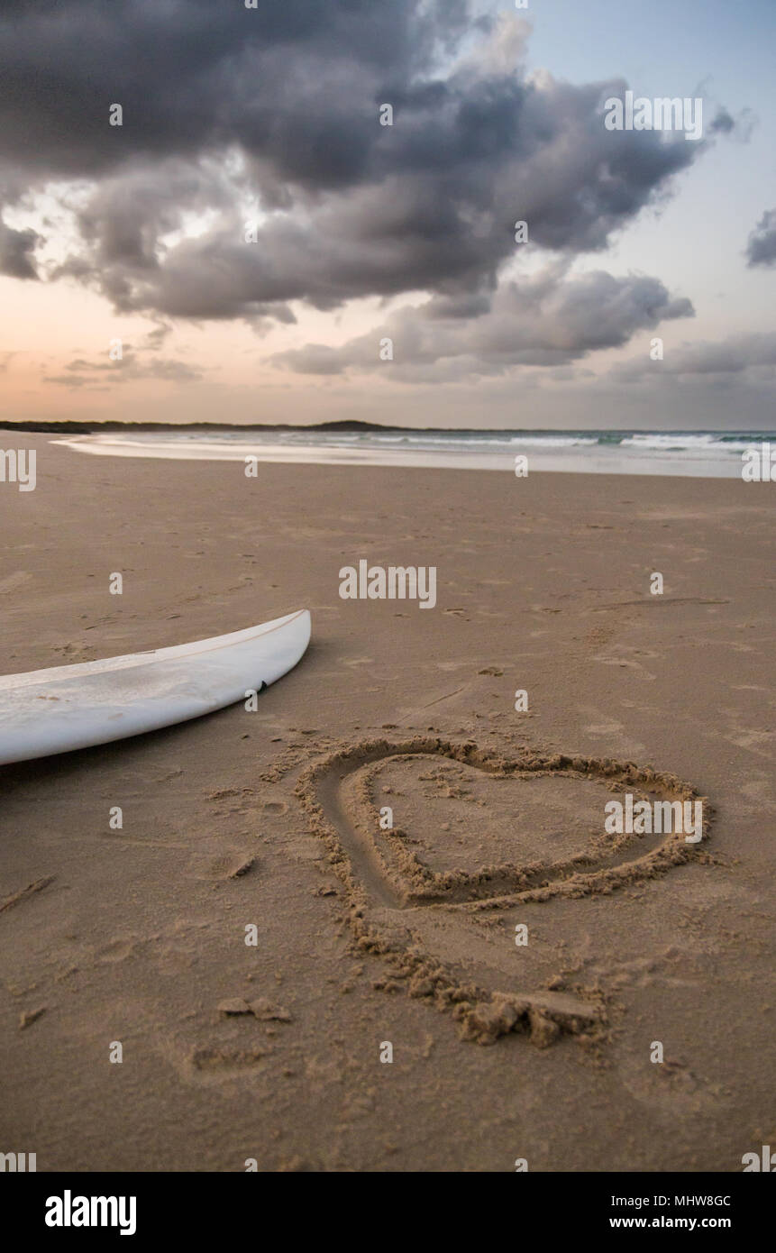 Love Heart drawn in sand next to a surfboard - Stock Image