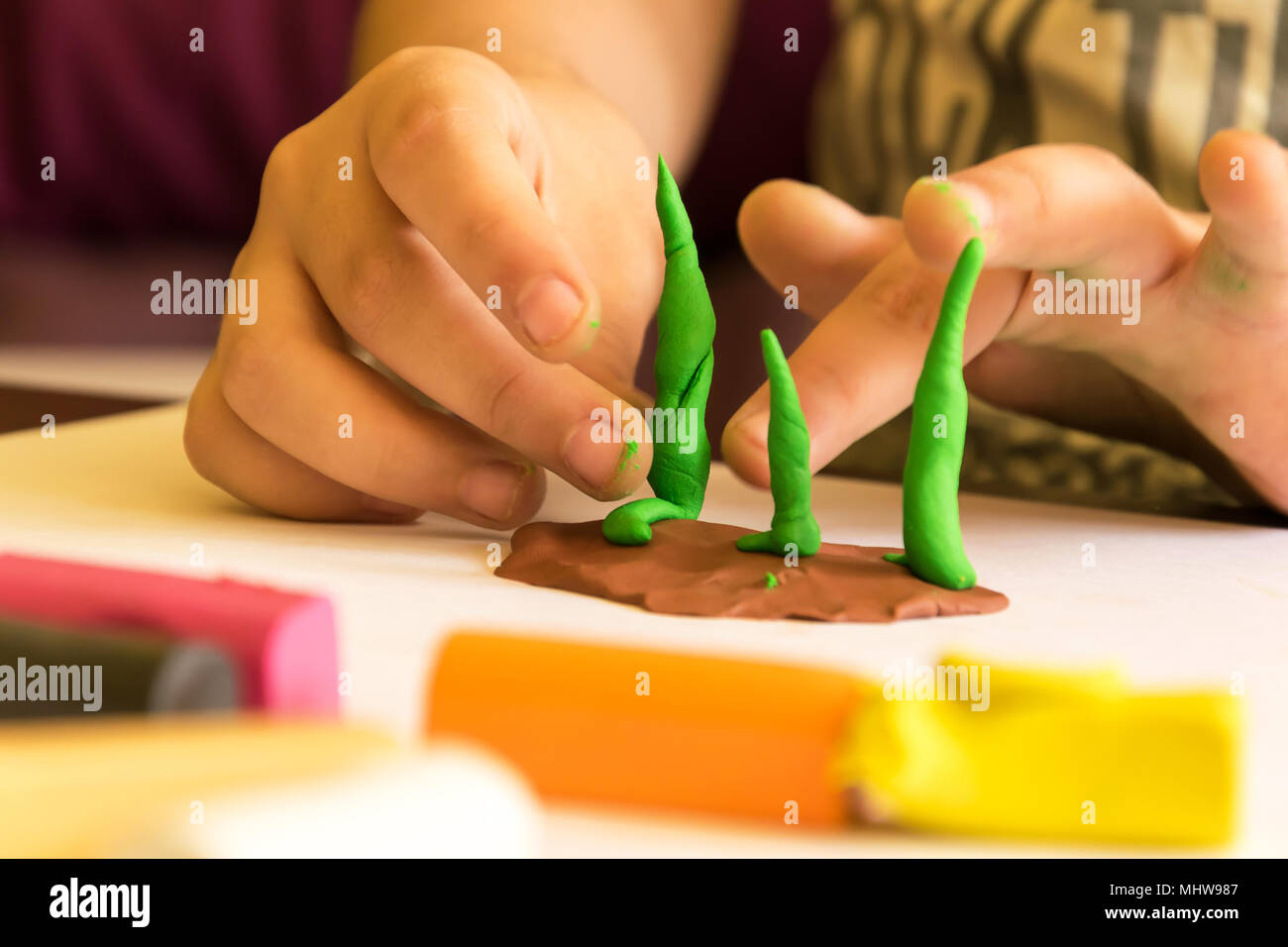 Child playing with plasticine, modeling tree. Developing imagination and creativity. - Stock Image