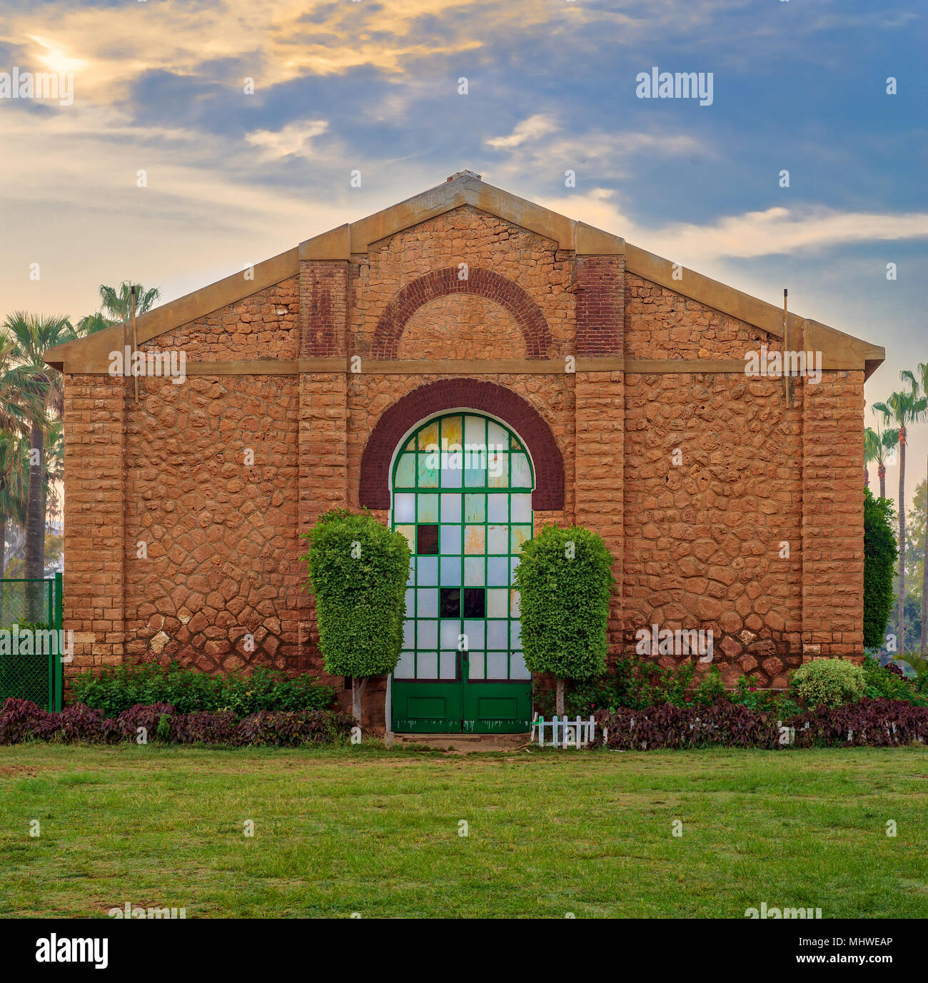 Side view of the Royal Plant Nursery with closed grunge door and orange painted bricks stone wall decorated with plants in sunrise time at Montaza pub - Stock Image