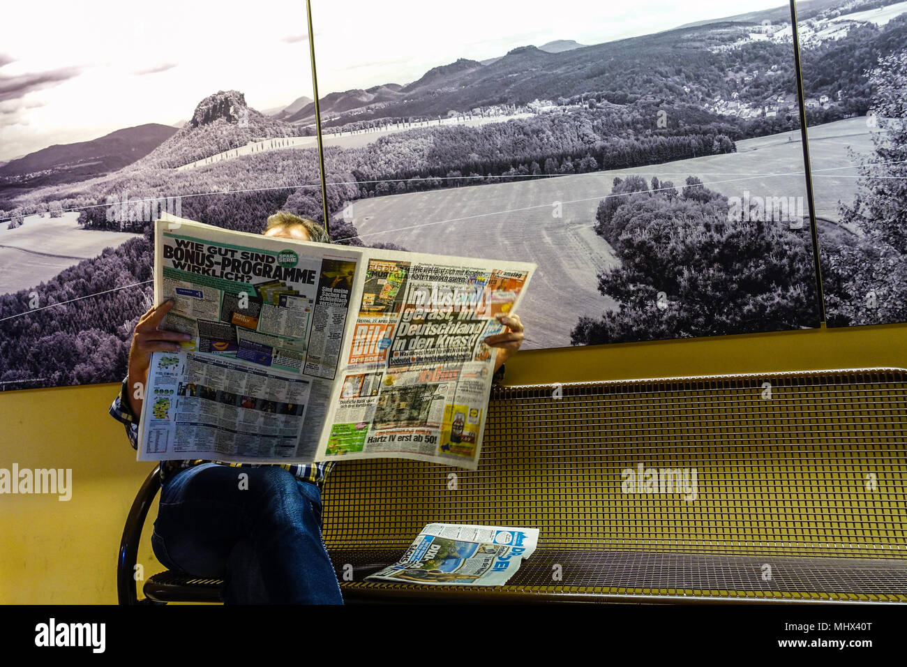 The reader reads the German newspaper Bild in the railway station, Bad Schandau, photo in the background is the landscape of Saxon Switzerland, German - Stock Image