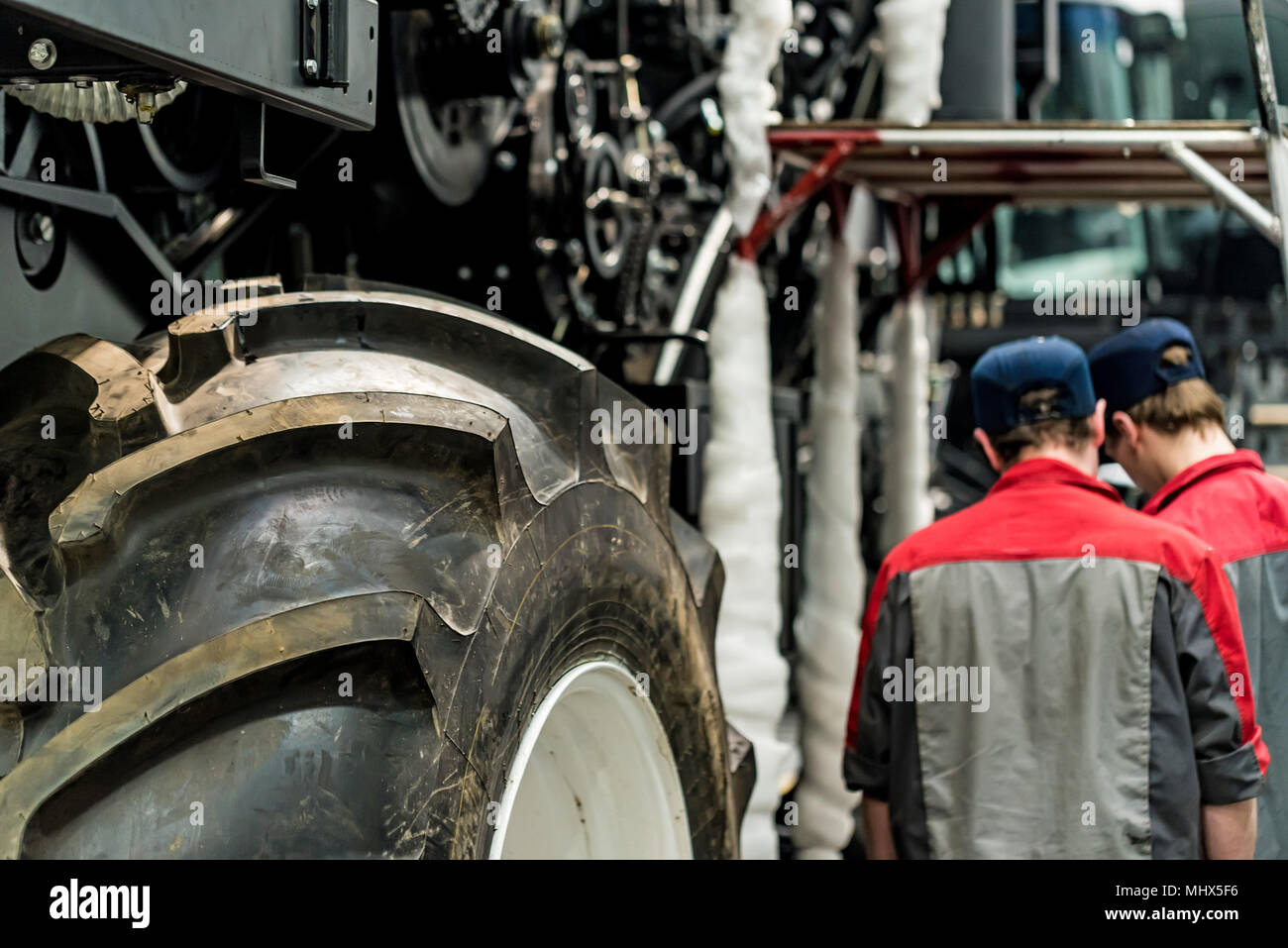 Worker assembles tractor or combine harvester at large machinery plant. Industrial concept of heavy machinery manufacturing - Stock Image