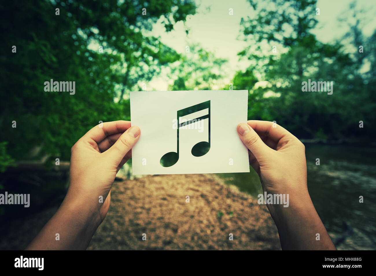 Woman Hands Holding A Paper Sheet With Music Note Inside In The
