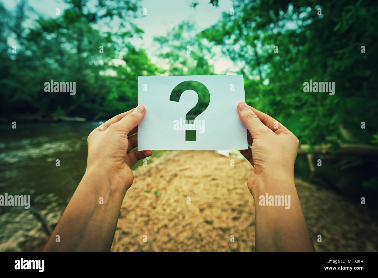 Close up of woman hands holding a paper sheet with the question mark inside, over green forest nature background. Lost people concept, global environm - Stock Image