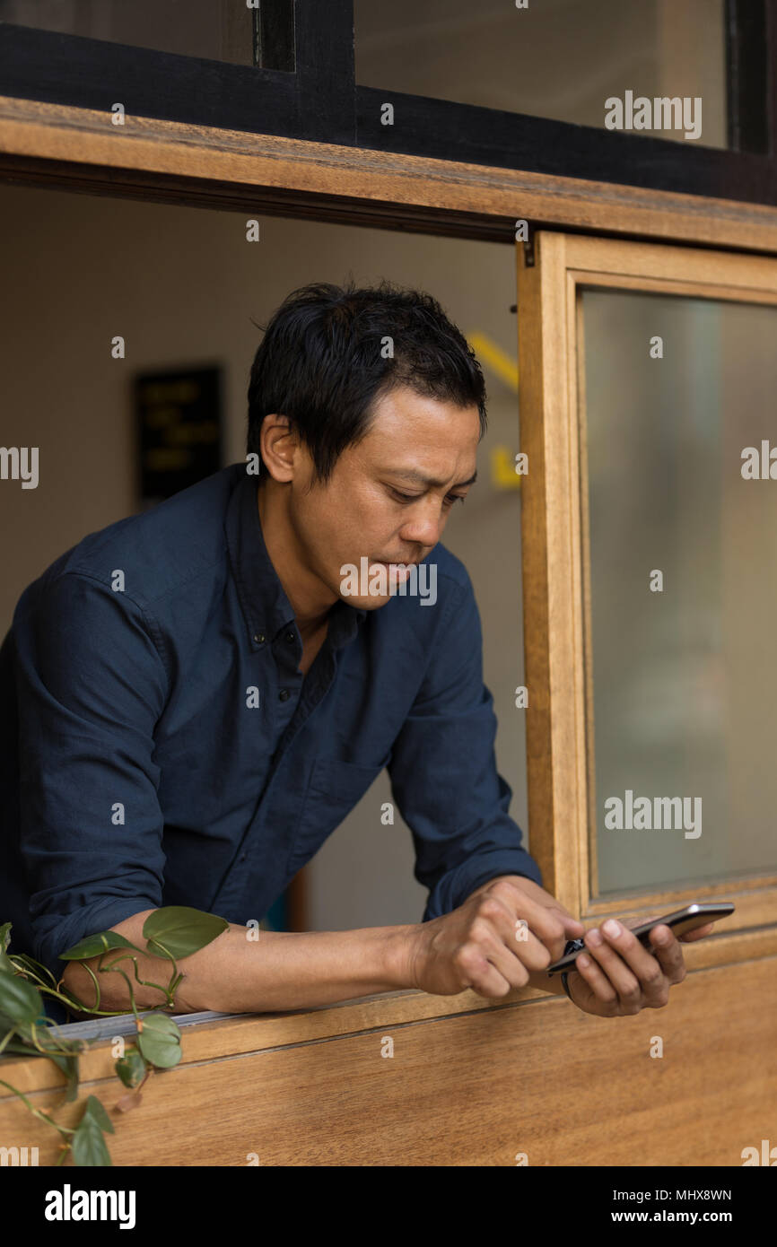 Businessman using moblie phone in the cafe - Stock Image