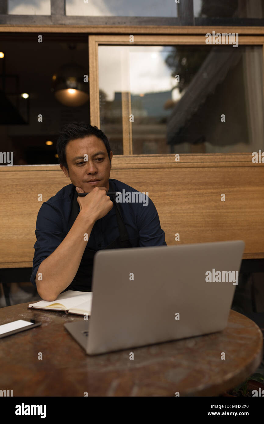 Thoughtful businessman looking at laptop - Stock Image