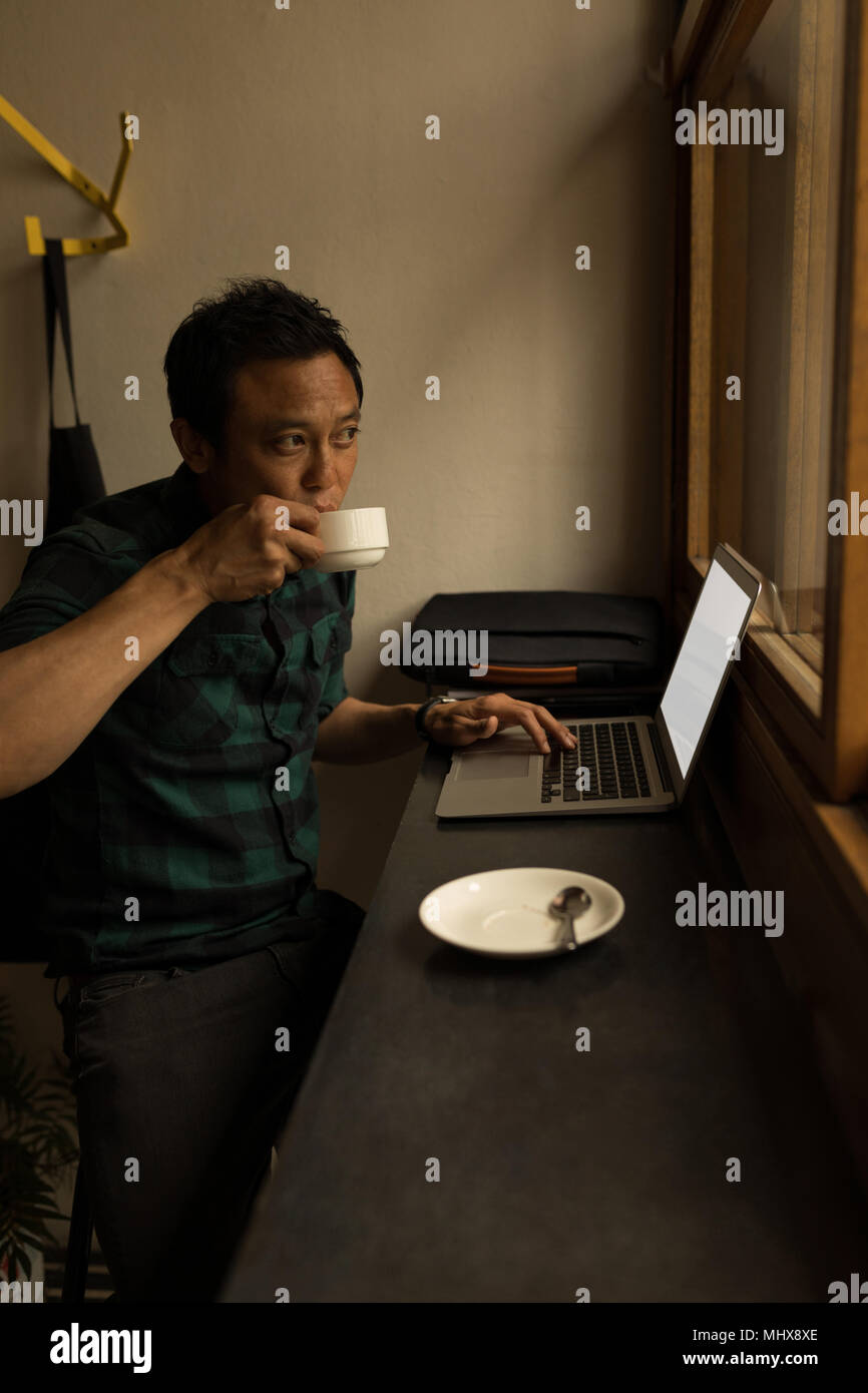 Businessman using laptop while having coffee - Stock Image