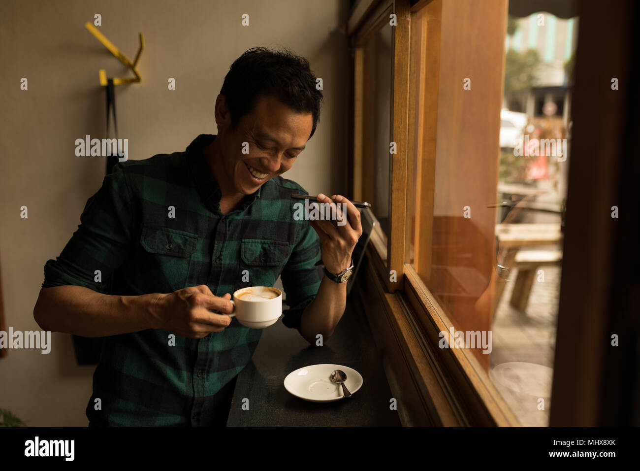Businessman talking on mobile phone while having coffee in the cafe - Stock Image