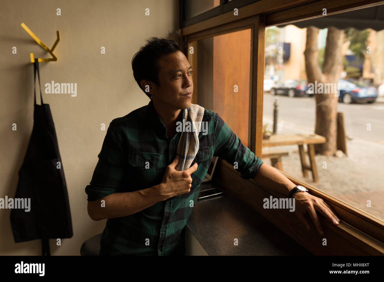 Thoughtful man looking through window - Stock Image