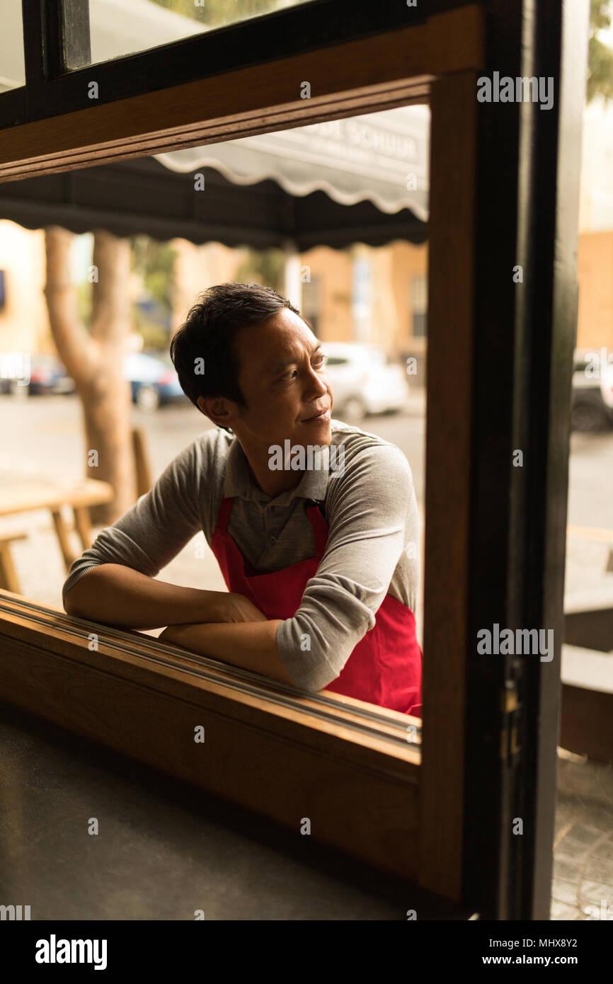 Staff looking backward near a window - Stock Image