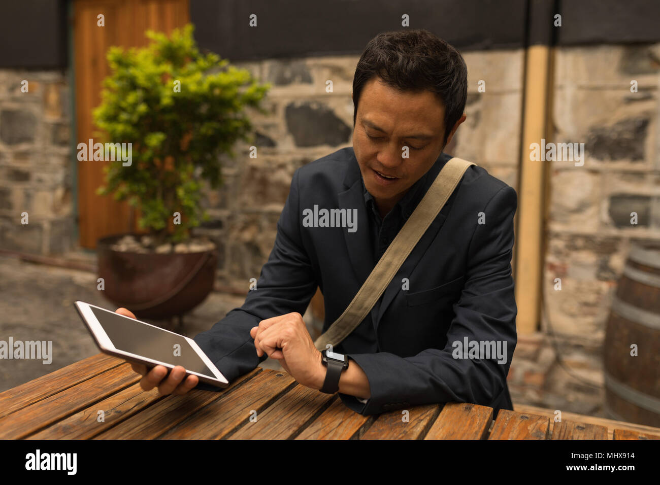 Businessman looking at smartwatch in the pavement cafe - Stock Image
