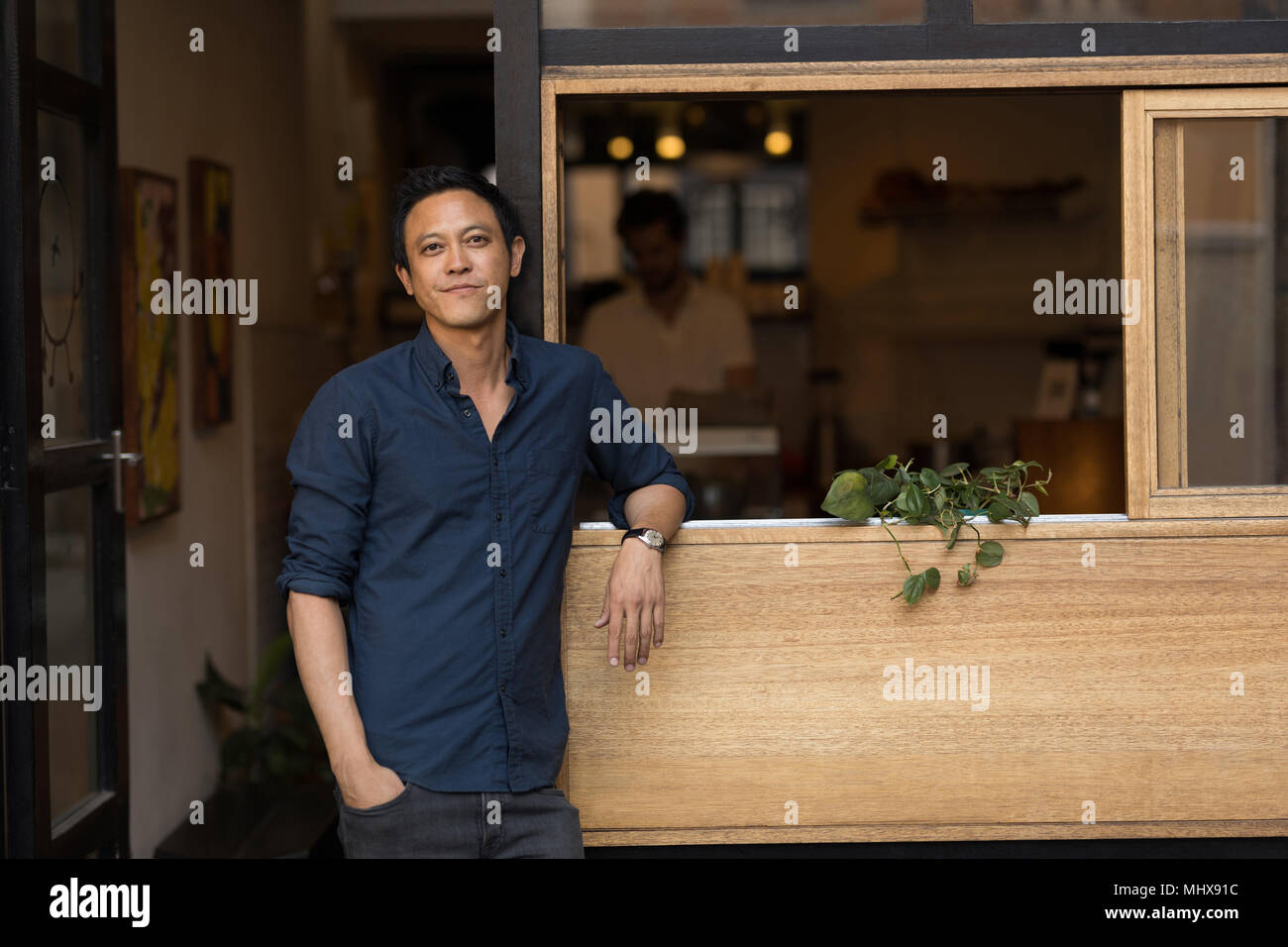 Businessman standing near window in the cafe - Stock Image