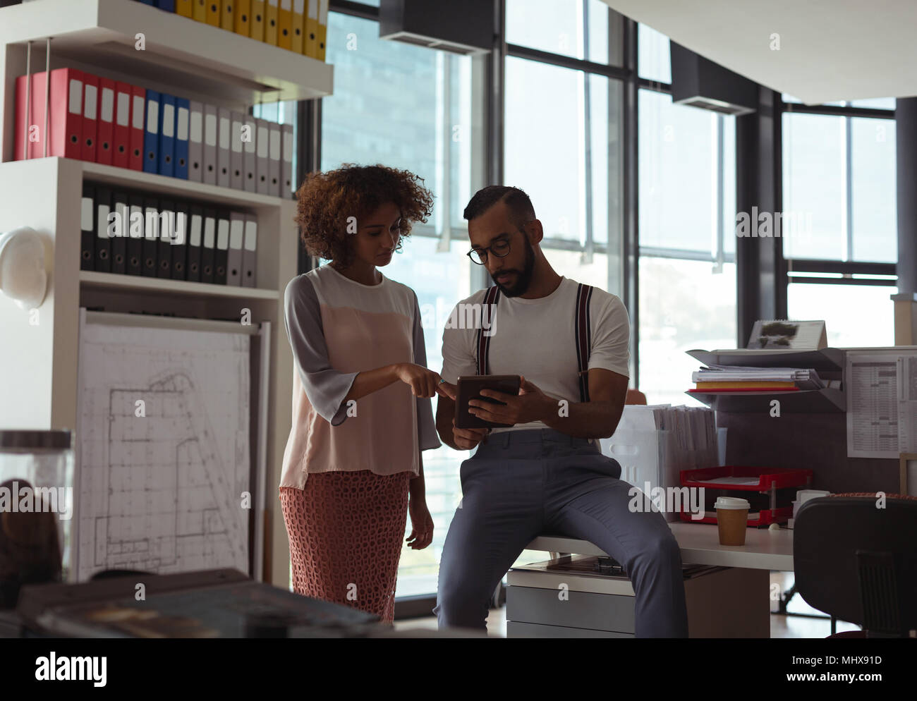 Architects discussing over digital tablet - Stock Image