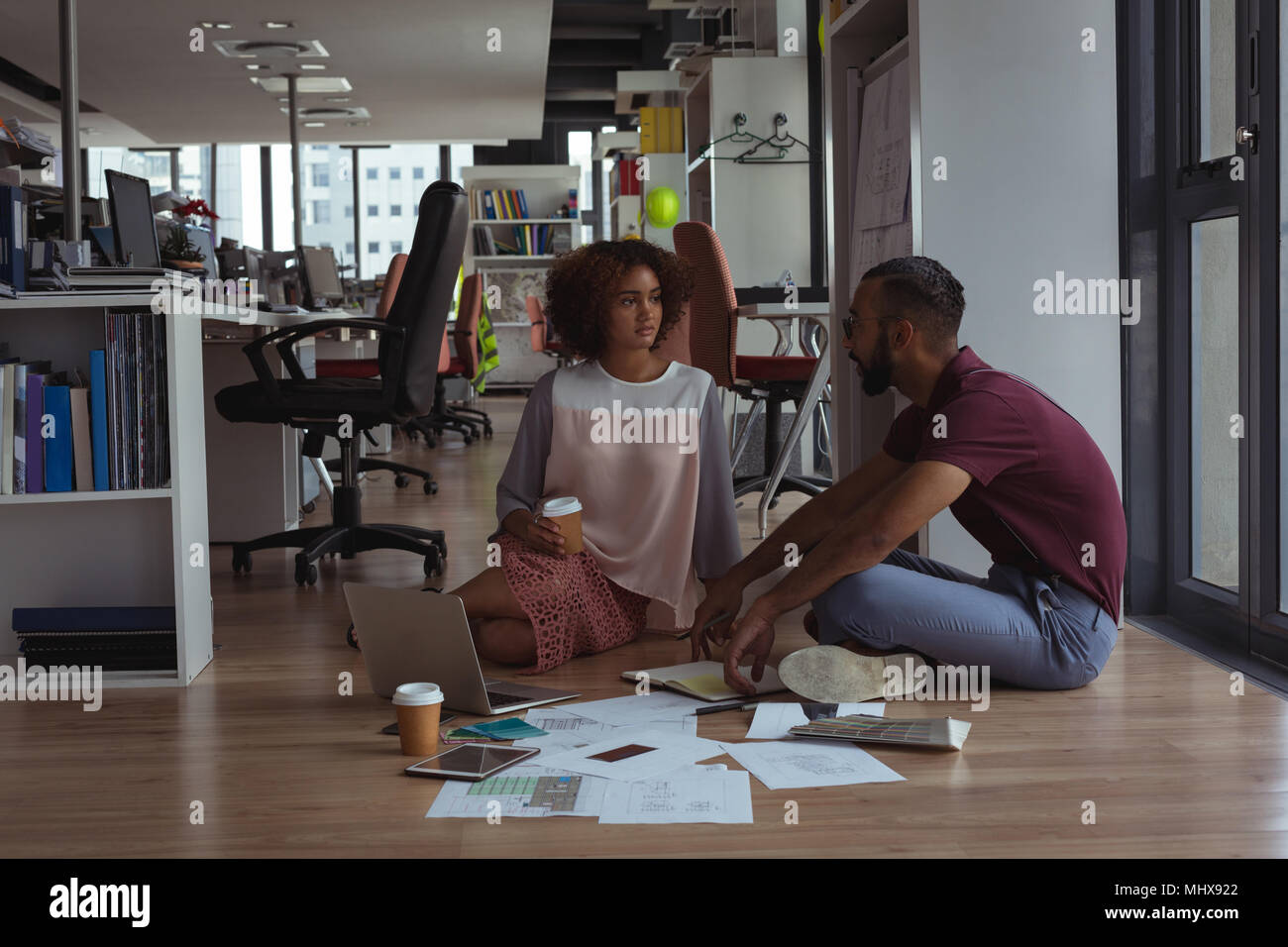 Architects interacting with each other on floor - Stock Image