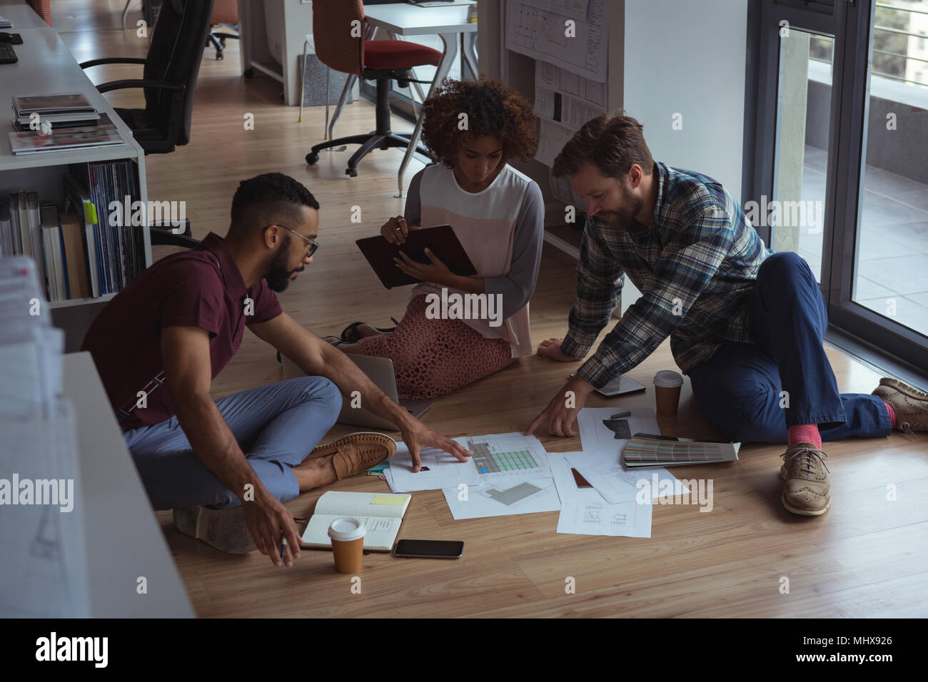 Architects discussing over document on floor - Stock Image