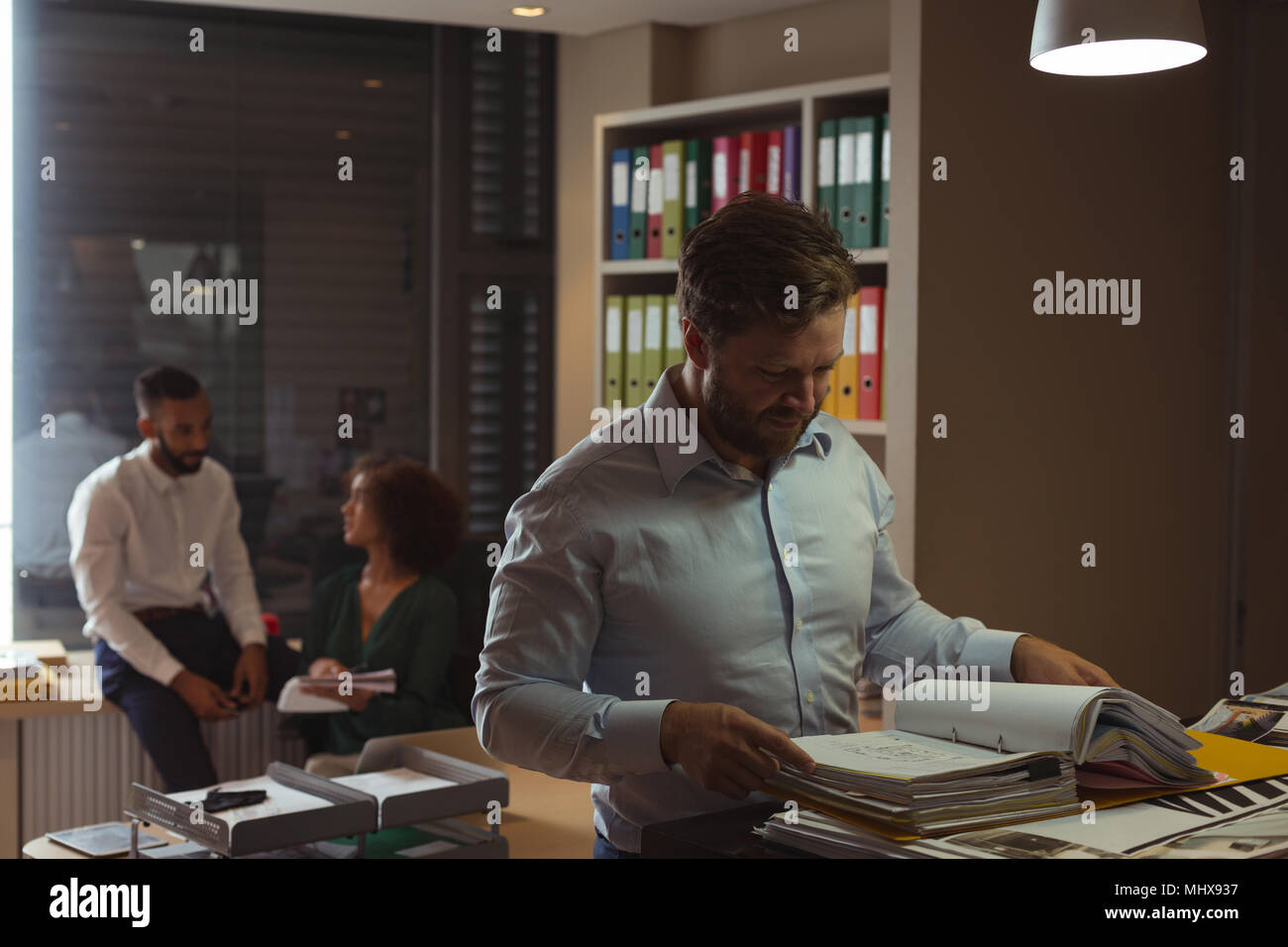 Architect checking file while colleagues interacting in background - Stock Image