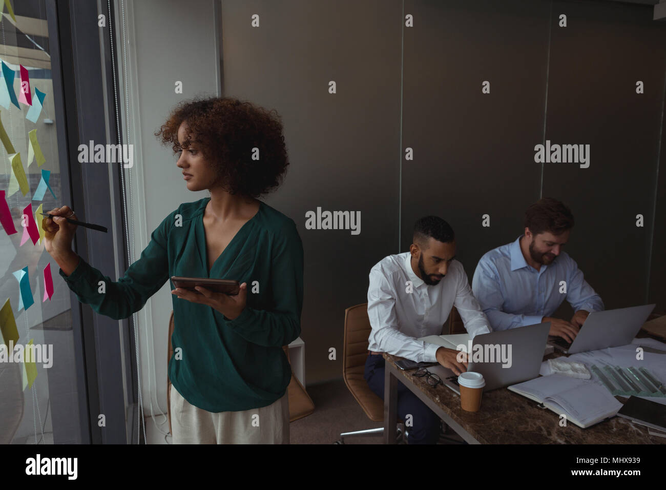 Female Architect with digital tablet writing on sticky note while colleagues using laptop Stock Photo