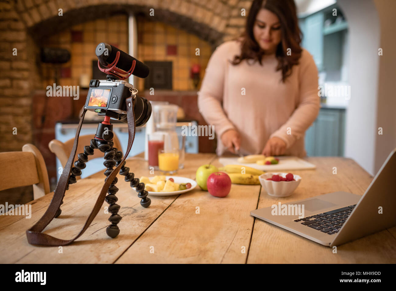 Female vlogger cutting fruit on chopping board - Stock Image