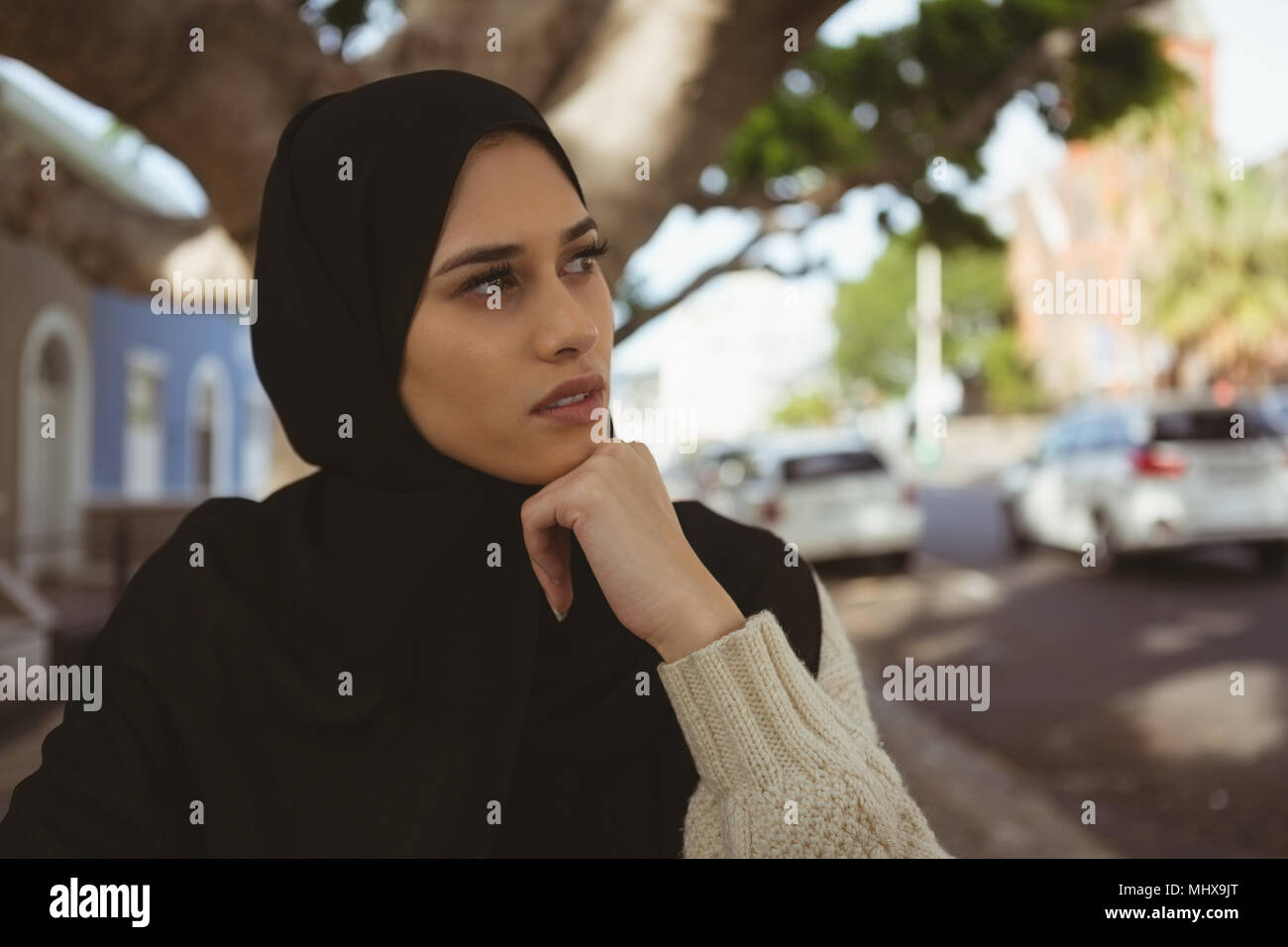 Thoughtful hijab woman at pavement cafe - Stock Image