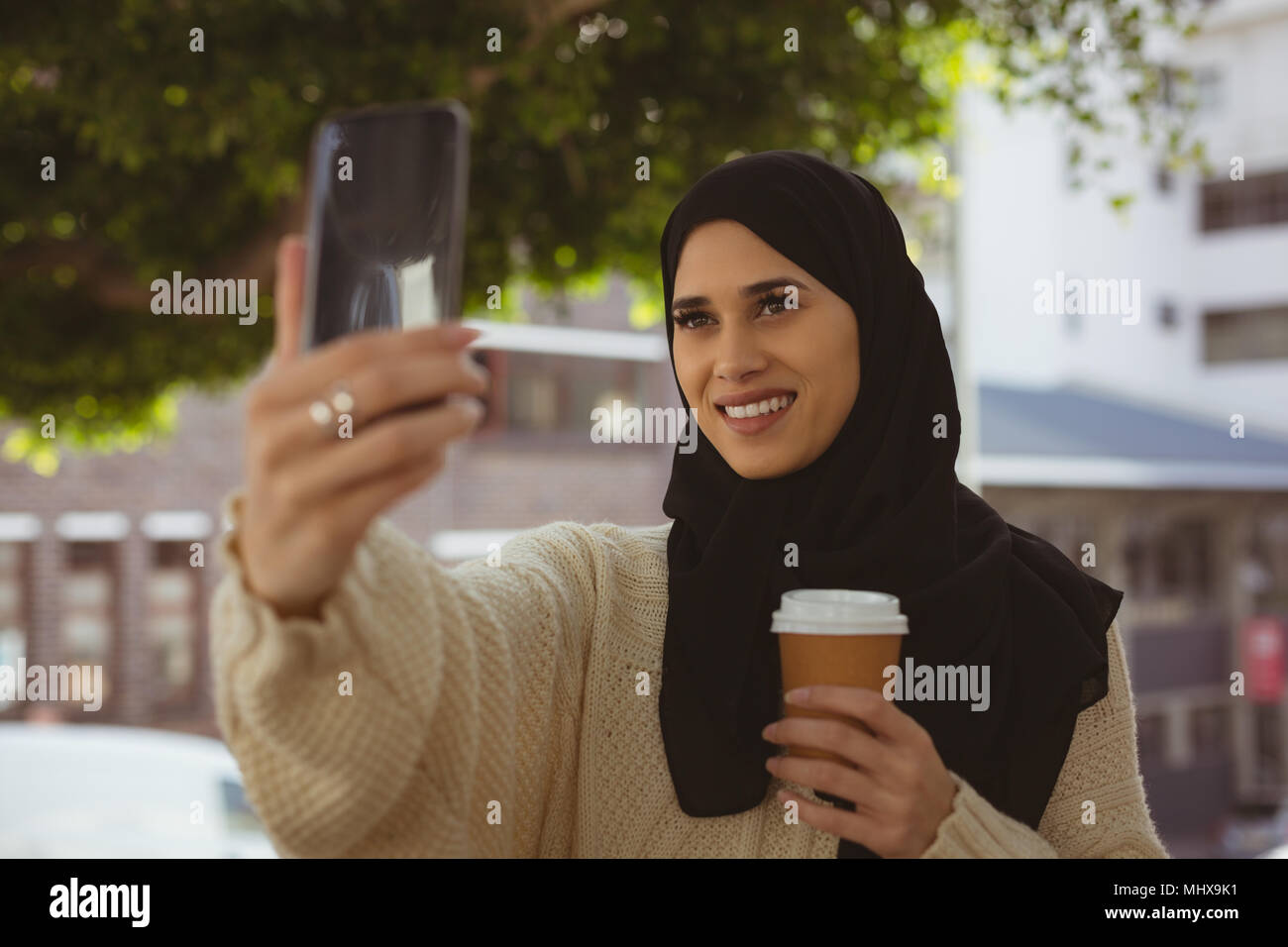 Hijab woman taking selfie with mobile phone - Stock Image