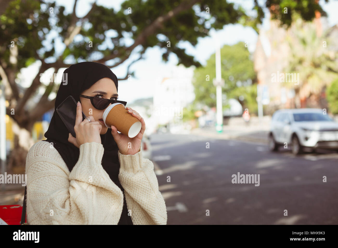 Hijab woman talking on mobile phone while having coffee at pavement cafe - Stock Image
