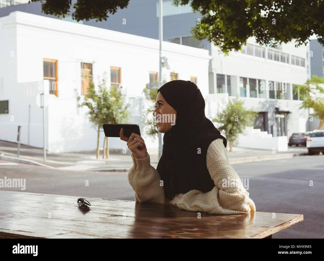 Urban hijab woman talking on mobile phone at pavement cafe - Stock Image