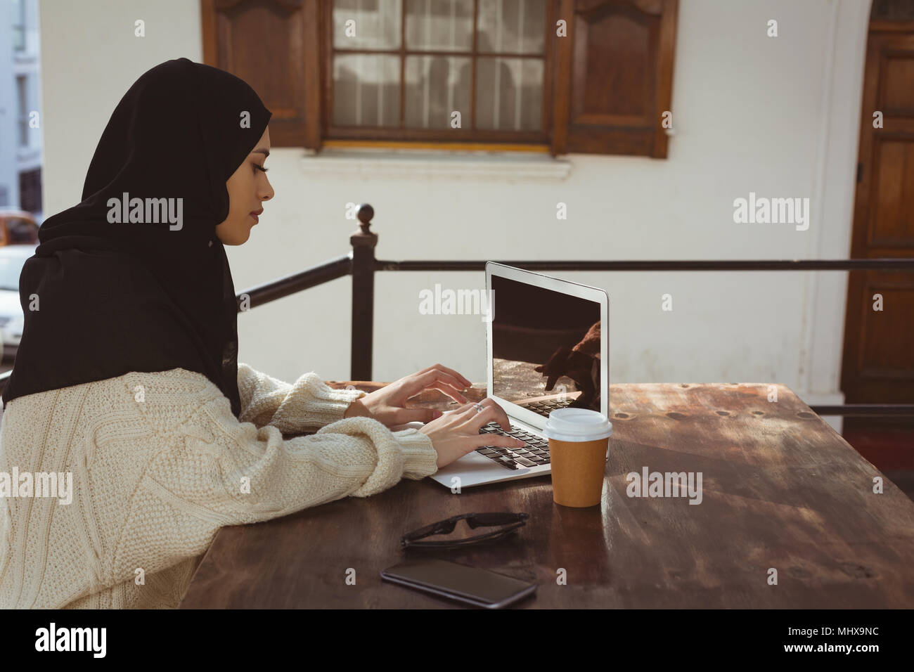 Hijab woman using laptop on table - Stock Image