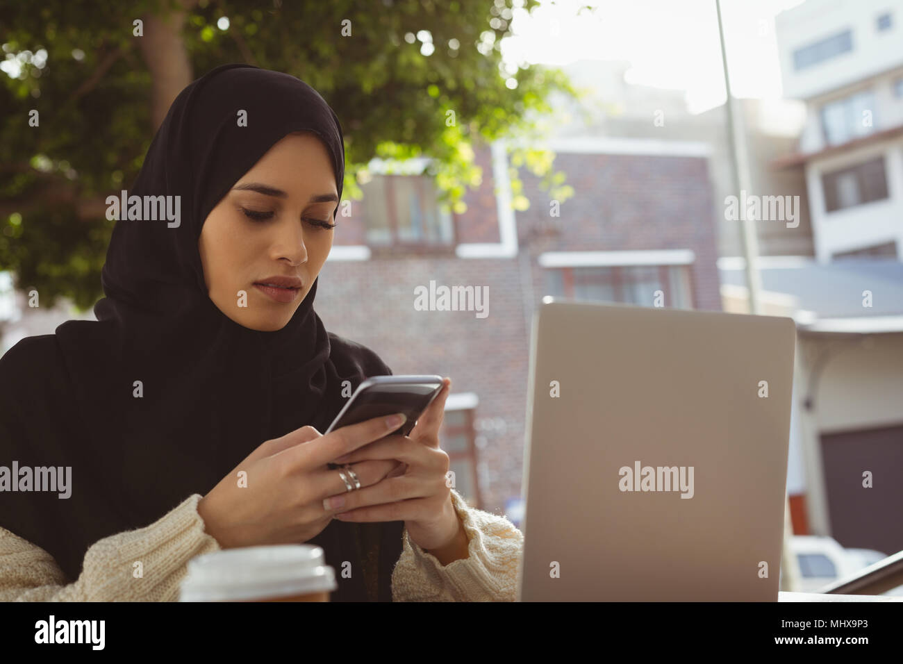 Hijab woman using mobile phone at pavement cafe - Stock Image