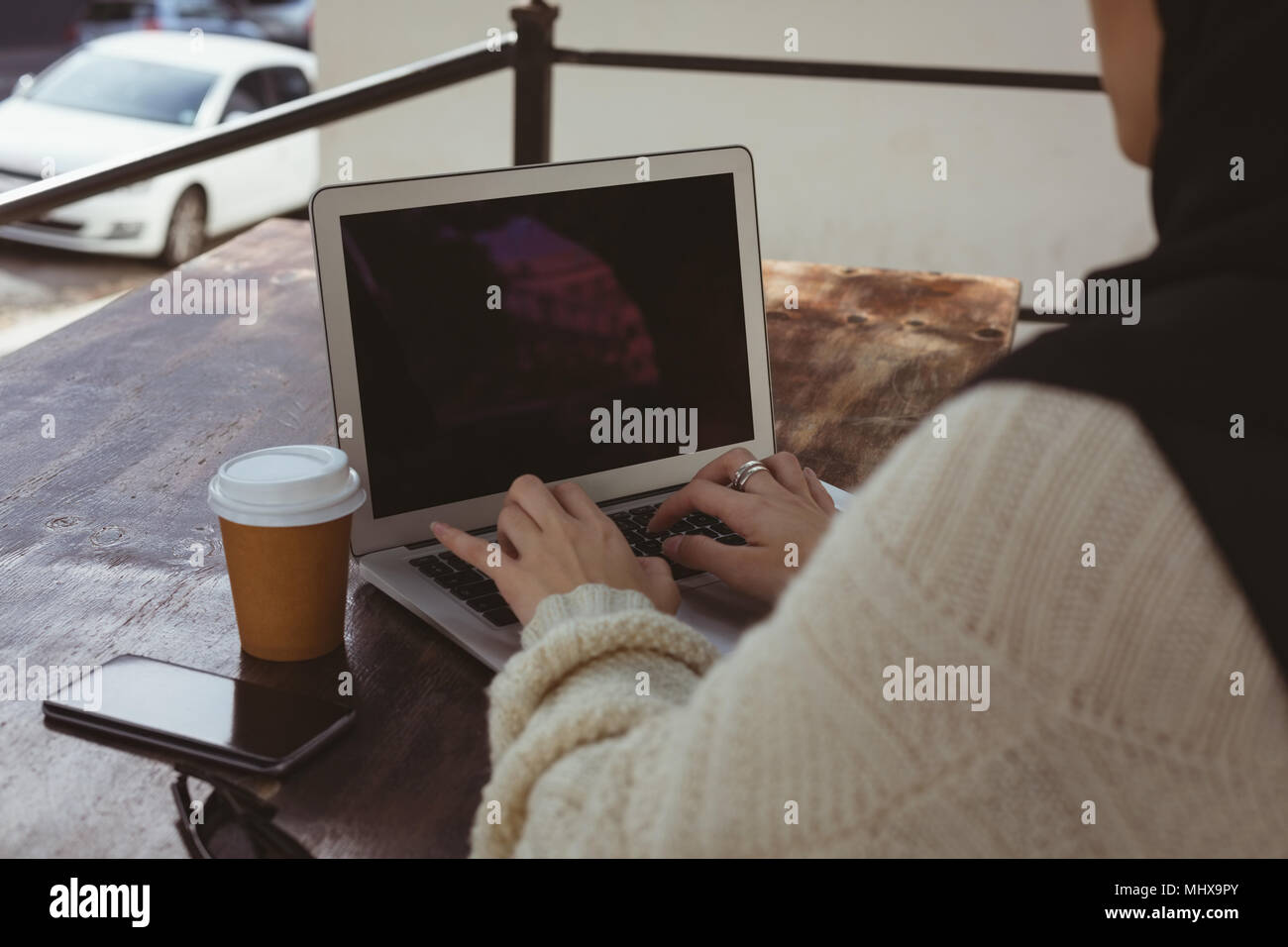 Urban hijab woman using laptop in pavement cafe - Stock Image
