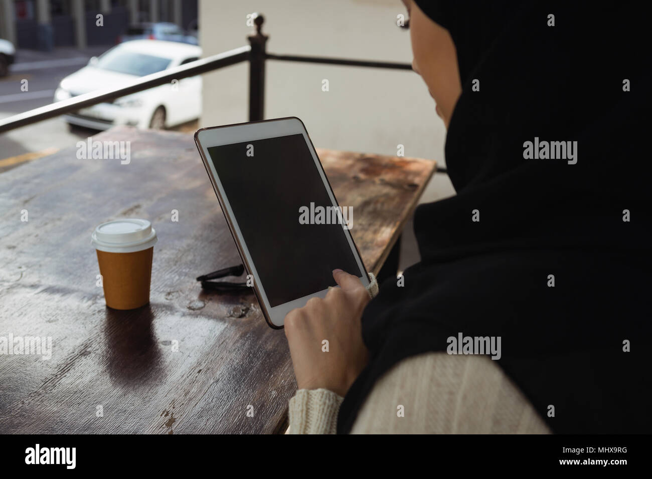 Hijab woman using digital tablet in cafe - Stock Image