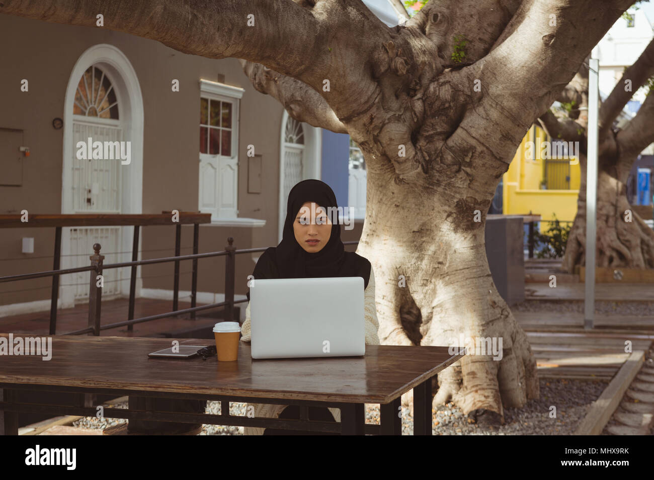 Urban hijab woman using laptop at pavement cafe - Stock Image